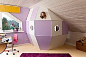 DIY space capsule made from white and purple wooden panels under sloping ceiling in child's bedroom; girl peeping through spy-hole