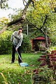 Man raking leaves in garden