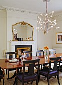 Original, antique dining table, reproduction chairs, whimsical designer chandelier and antique mirror above fireplace
