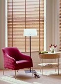 Magenta armchair, modern, elegant standard lamp and small, designer table in front of wooden louvre blinds on bay window