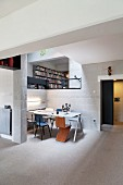 Dining area with Bauhaus chairs around table in open-plan interior with breeze block walls