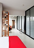 Bed with red bedspread in open-plan interior opposite frosted glass wall with black, steel frame