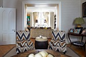 Easy chairs with zig-zag upholstery and drum-shaped side table in living area with symmetrical furnishings