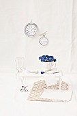 Forget-me-nots in teacup and dolls'-house furnishings with tiny clocks on wall