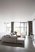 Pale grey corner in elegant living room with grey epoxy floor and view of lake