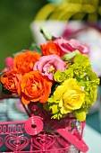 Colourful bouquet in wire basket outdoors