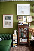 Green Chesterfield sofa, antique display case and pictures on green wall