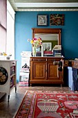 Stacked magazines on top of antique cabinet with mirror against blue wall