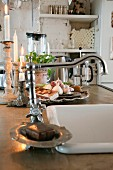 Kitchen counter with integrated sink and vintage tap fittings; lit candles next to dish of garlic bulbs in background