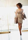 Geschäftsfrau auf dem Weg zur Arbeit mit Coffee to go und Smartphone