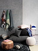 Various pouffes and cushions on floor against grey wall with scarves hanging from hooks
