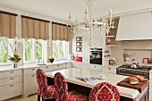 White country-house kitchen with free-standing counter and bar stools upholstered in red and white brocade below white chandelier