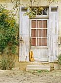 Baguettes leaning against rustic door; Aquitaine, France
