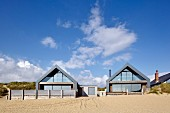 Camber Sands Beach Houses, Rye, United Kingdom. Architect: Walker and Martin, 2014; View of houses looking up from the beach