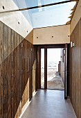 Camber Sands Beach Houses, Rye, United Kingdom. Architect: Walker and Martin, 2014; View through front door and hallway directly onto sandy beach and sea