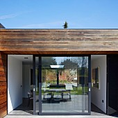 Point 7, Winchester, United Kingdom. Architect: Dan Brill Architects, 2014. View from terrace through sliding doors into interior of contemporary house