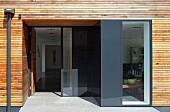 Ausschnitt eines zeitgenössischen Wohnhauses mit horizontaler Holzverschalung, zurückgesetzter Eingang, Blick durch offene Tür in Hausflur