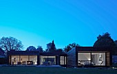 Point 7, Winchester, United Kingdom. Architect: Dan Brill Architects, 2014. Exterior of contemporary house complex with illuminated interior at dusk