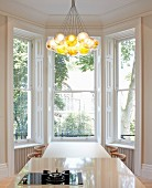 Private Apartment, London, United Kingdom. Architect: Hill Mitchell Berry, 2014. Spherical pendant lamps above dining table in front of bay window