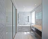 Edles Marmorbad, seitlich minimalistischer Waschtisch, vor Badewanne am Fenster