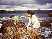 Bruder und Schwester spielen auf felsigen Strand