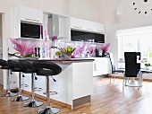 White fitted kitchen with magnolia-patterned splashbacks, leather bar stools at counter and dining area in background next to window in open-plan interior
