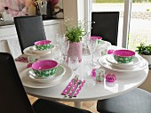Place settings with colourful bowls on round table with black, leather-covered chairs