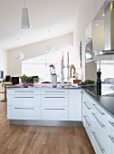 Fitted kitchen with white cabinets and stainless steel strip handles in open-plan interior
