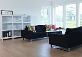 Blumige Kissen auf schwarzen Sofas und halbhohe Vitrine in puristischem Wohnraum, im Hintergrund eine Fensterfront zum Garten