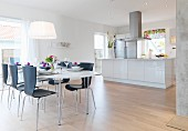 Festively set oval table and black chairs in light-flooded interior with open-plan designer kitchen