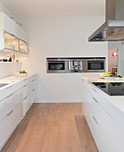 White designer kitchen with illuminated wall units, island counter and stainless steel appliances integrated in wall
