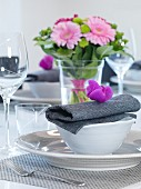 Festive place setting with white china crockery and purple flower on grey linen napkin in front of vase of flowers