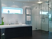Bathroom in austere light grey, charcoal and white with floor-level twin shower behind glass screen