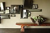 Spiegelkollage an der Wand über verzierter Holzbank mit Gefäss-Skulptur