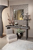 Arrangement in silver grey with sculptures, lamps, console table, mirror and easy chair with fringed trim