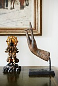Sculpture of hand and figurine on antique cabinet in front of corner of painting