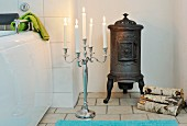 Lit, white candles in floor candlestick, iron stove and small log pile in bathroom