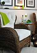Wicker armchair with white cushions and side table with wine bottle and wine glasses in candlelight atmosphere