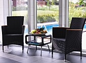 Rattan chairs flanking fruit bowl on retro side table in front of floor-to-ceiling windows with view of pool in garden