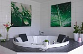 Whirlpool tub in white-tiled bathroom below pictures with leaf motifs on wall