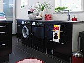 Modern laundry room with black appliances integrated into counter with black base units