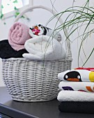 Stacked towels and white basket of rolled towels