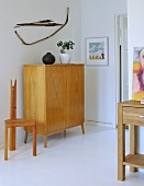 Half-height, fifties-style cabinet in pale, solid wood and hand-crafted chair in simple room