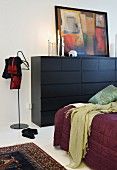 Partially visible bed, black chest of drawers and modern valet stand