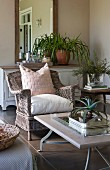 Stone coffee table on metal frame and comfortable rattan armchair on comfortable veranda