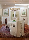 Armchair with pale loose cover, chairs around table with white tablecloth and chandelier in traditional, elegant dining room
