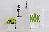 weiße Behälter mit Pflanze und Bürste, daneben Seifenspender und Küchenrolle