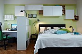 A room divider and wall cupboards hung at different heights to create lots of storage space between a double bed and a home office with a communal, green-painted wall