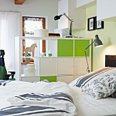A view from a bed of a room divider with closed elements in white and friendly green with retro-style lamps and bed clothes