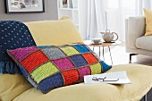 A colourful, homemade, crocheted patchwork cushion cover